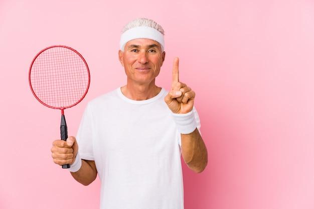 O homem envelhecido médio que joga o badminton isolou mostrar o número um com dedo.