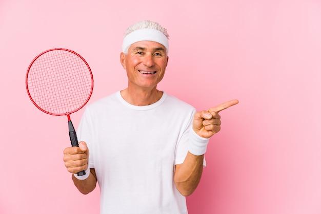 O homem envelhecido médio que joga o badminton isolou o sorriso e apontar de lado, mostrando algo no espaço em branco.