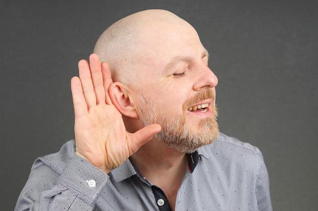 O homem ergueu os ouvidos para ouvir com a mão