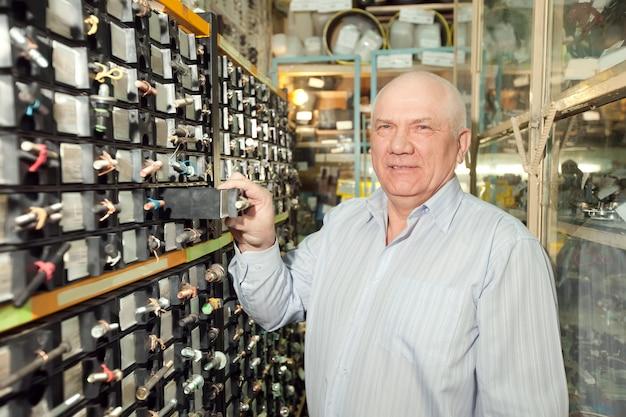 O homem escolhe os fechos na loja de peças de automóveis