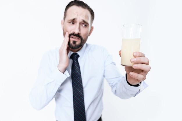 O homem espera enquanto o comprimido se dissolve na água.