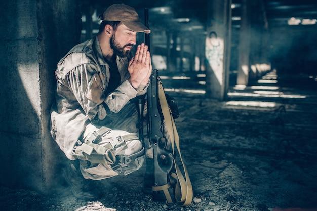 O homem espiritual está sentado em posição de agachamento e orando. ele mantém os olhos fechados e de mãos dadas perto do rosto. também há um rifle perto dos joelhos.