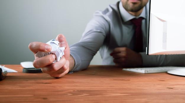 O homem espremeu o papel em uma bola.