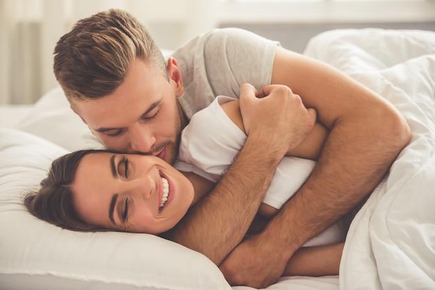 O homem está abraçando e beijando sua esposa sorridente na bochecha