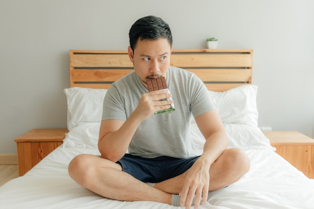 O homem está bebendo uma xícara de café na cama em seu quarto.
