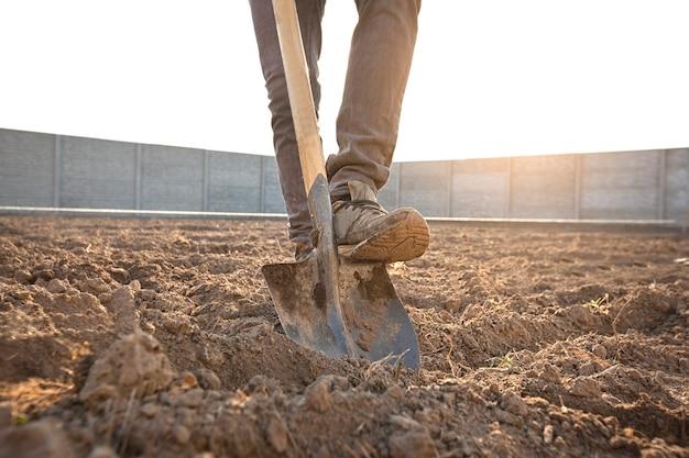 O homem está cavando o solo de sua casa de campo
