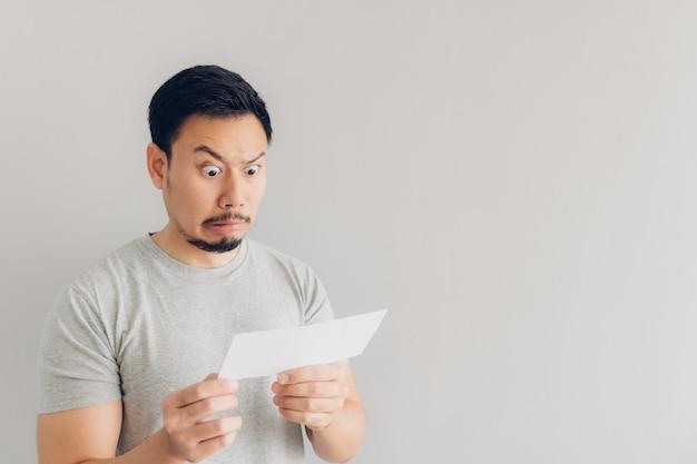 O homem está chocado e surpreso com a mensagem de correio branco ou a conta.