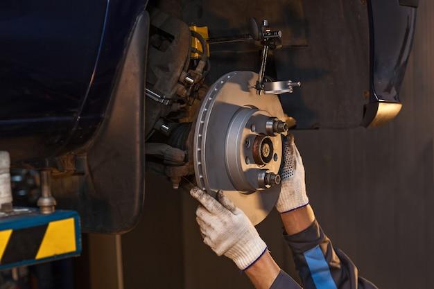 O homem está consertando o freio a disco do carro. reparo do freio a disco.