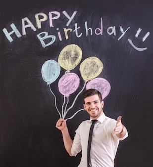 O homem está de encontro ao balão e ao feliz aniversario de tiragem.