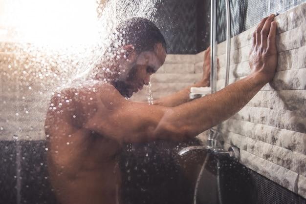 O homem está debruçado na parede ao tomar o chuveiro no banheiro.