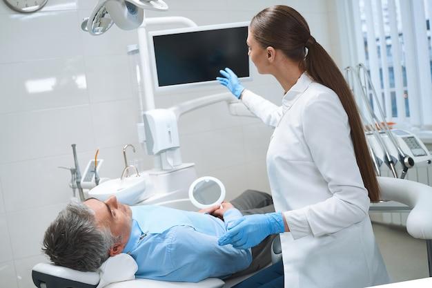 O homem está deitado na cadeira de dentista enquanto o especialista o trata com a ajuda de tecnologias modernas