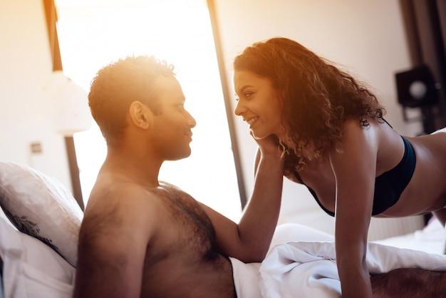 O homem está deitado na cama e a mulher está se aproximando dele eroticamente.