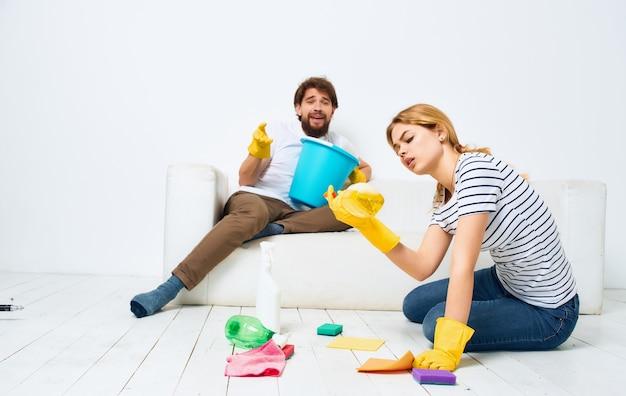 O homem está deitado no sofá e a mulher está limpando o detergente do chão