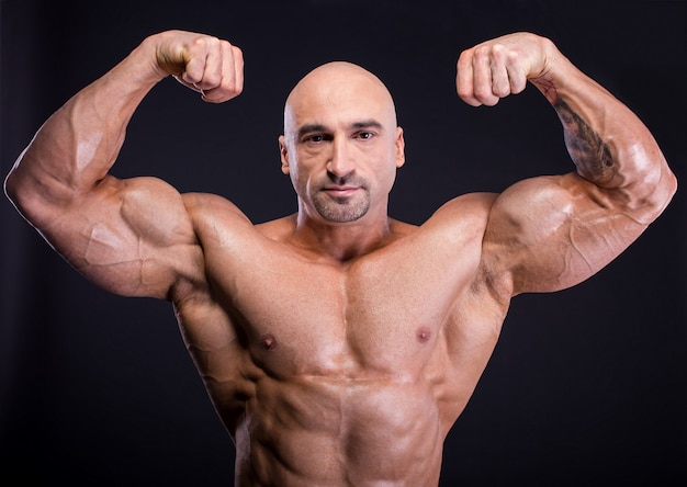 O homem está demonstrando seu perfeito corpo musculoso.