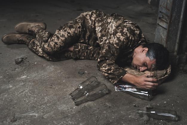 O homem está dormindo bêbado no porão.