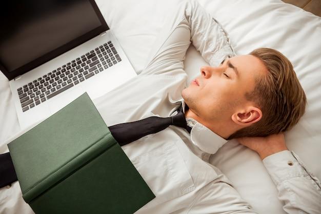 O homem está dormindo e mantendo as mãos atrás da cabeça.