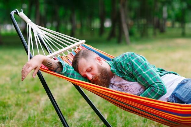 O homem está dormindo na rede