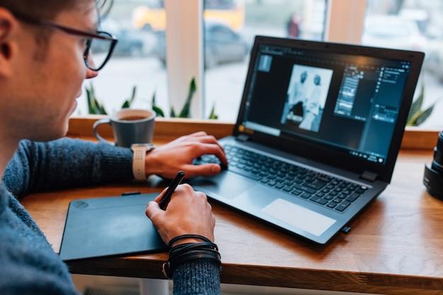 O homem está editando fotos no laptop, usando a mesa digitalizadora e o visor interativo com caneta