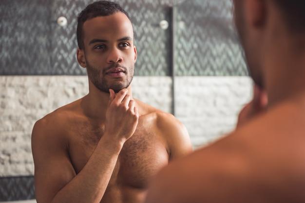 O homem está examinando sua face ao olhar no espelho.
