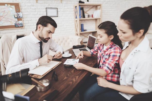 O homem está falando com clientes mulher e filha.