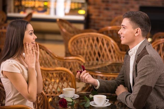 O homem está fazendo proposta com o anel para sua namorada.
