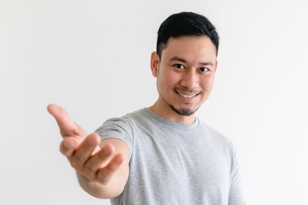 O homem está fazendo um gesto de convite ou oferece ajuda.