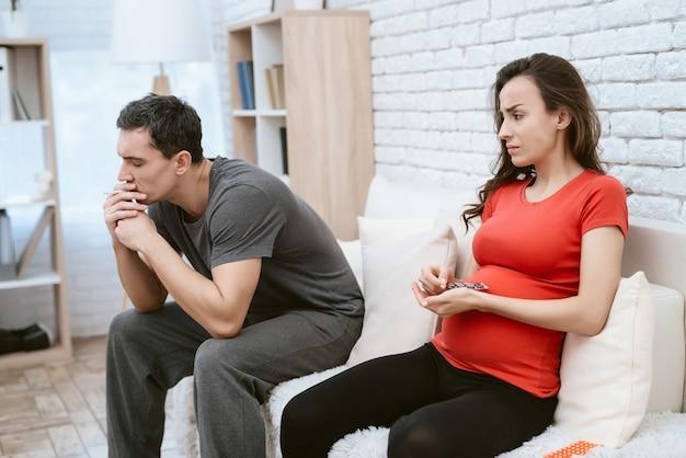 O homem está fumando um cigarro ao lado dele é sua esposa grávida.