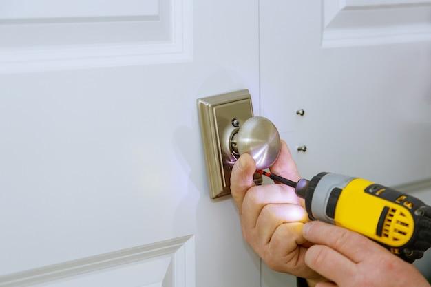 O homem está instalando a nova fechadura falsa da porta pela chave de fenda