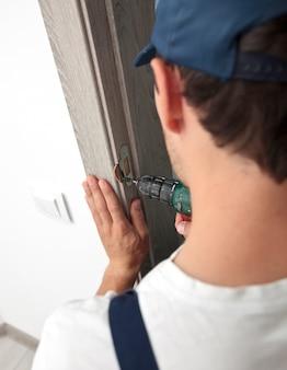 O homem está instalando a parte da porta de madeira pela chave de fenda