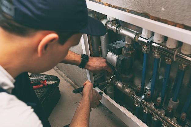 O homem está instalando o sistema de aquecimento na casa