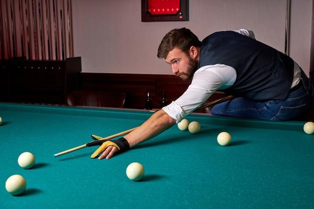 O homem está jogando sinuca, o jovem está com o objetivo de lançar a bola de sinuca cara bonito de mãos dadas na mesa de sinuca. bilhar