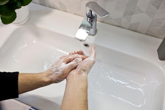 O homem está lavando as mãos com sabão no banheiro