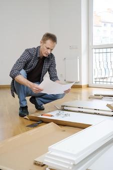 O homem está lendo as instruções para montar móveis.