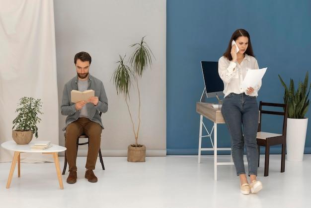 O homem está lendo enquanto a mulher fala no celular