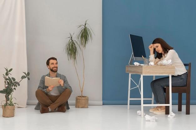O homem está lendo enquanto a mulher trabalha no computador