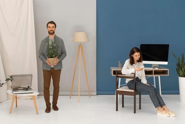 O homem está lendo enquanto a mulher usa o celular