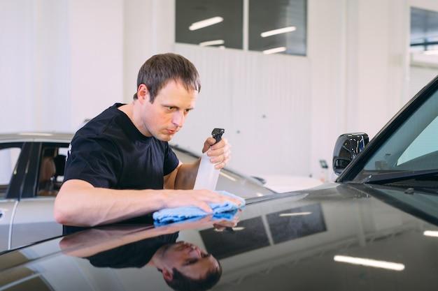 O homem está limpando com o corpo de pano de um carro brilhante.
