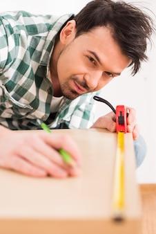 O homem está medindo a placa de madeira com fita de medição.
