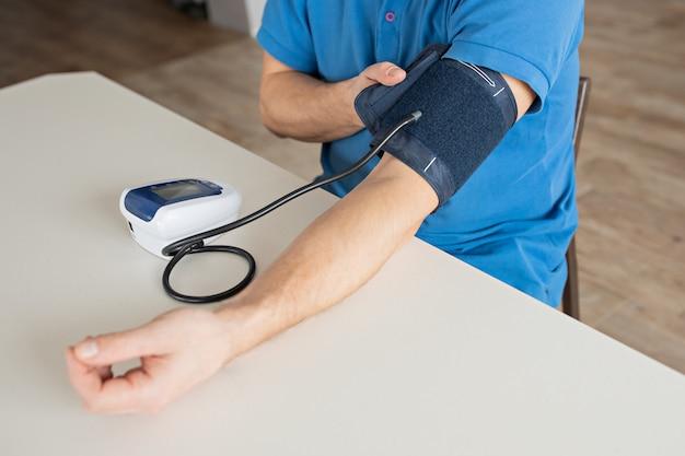 O homem está medindo a pressão sanguínea com o monitor na casa.