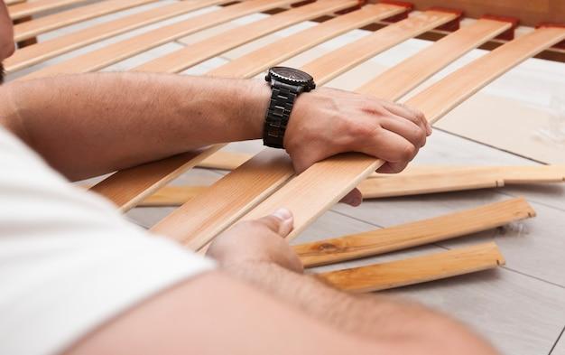 O homem está montando móveis de madeira em casa