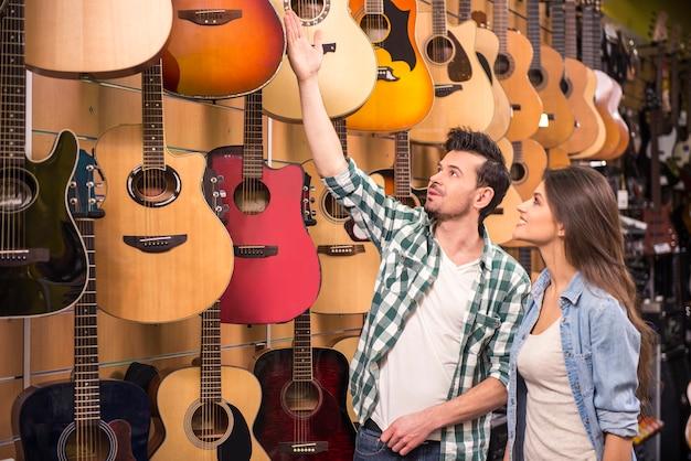 O homem está mostrando à guitarra da menina em uma loja da música.