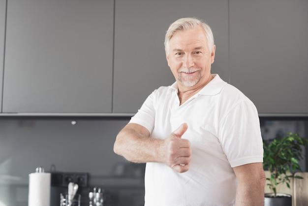 O homem está na cozinha. ele mostra o polegar para cima.