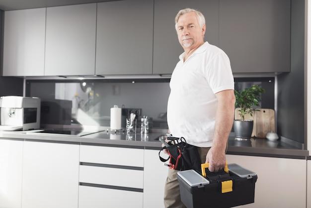 O homem está na cozinha. ele tem uma caixa de ferramentas preta nas mãos.