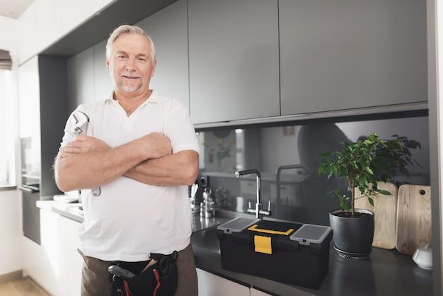 O homem está na cozinha. ele tem uma chave de cromo na mão.