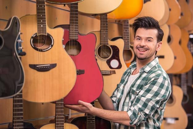 O homem está olhando e segurando a guitarra na loja de música.