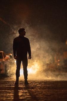 O homem está parado na rua enfumaçada. noite à noite. foto com lente telefoto