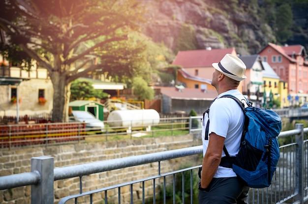 O homem está parado olhando para a montanha na vila