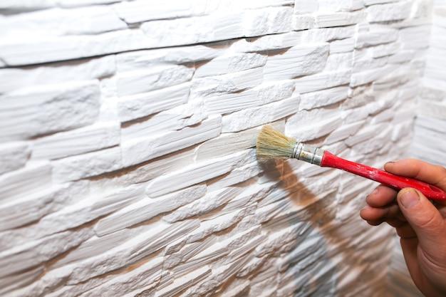 O homem está pintando a parede com pincel. tijolos decorativos e fundo de concreto. obras de reparação de manutenção. reforma no apartamento. restauração dentro de casa.