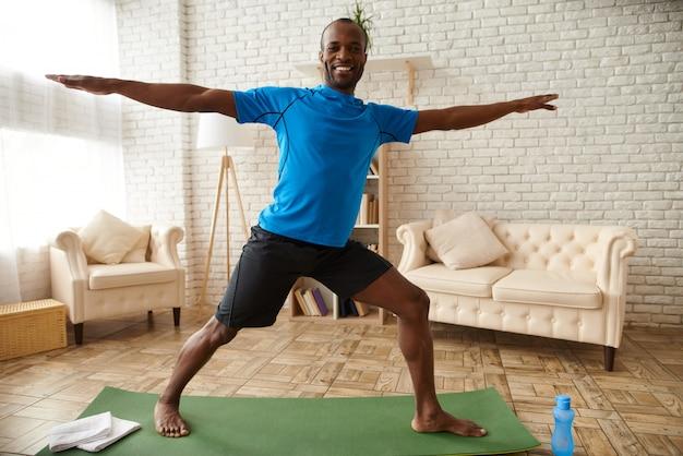 O homem está praticando yoga avançado em casa