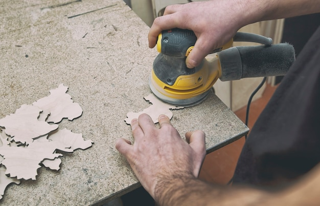 O homem está processando com madeira por máquina de polimento